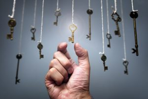 a hand reaching for a key hanging among other keys glowing