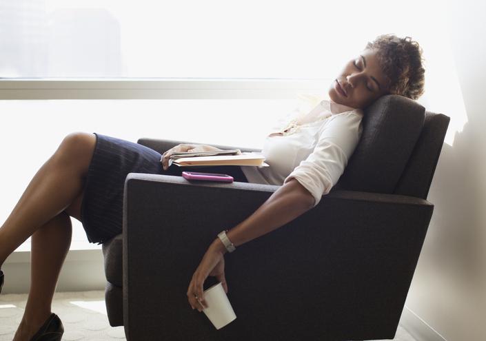 Businesswoman sleeping in office chair