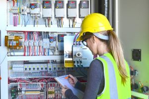 Female Inspector checking electric panels
