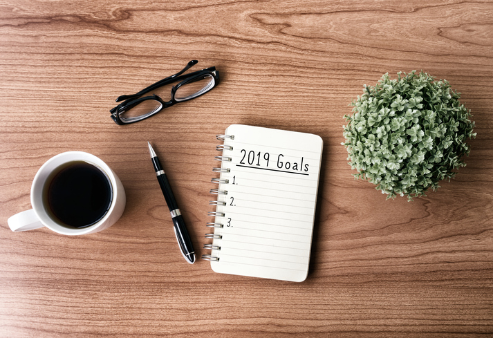 New year goals and resolution concept - 2019 goals text on notepad. Retro style background.