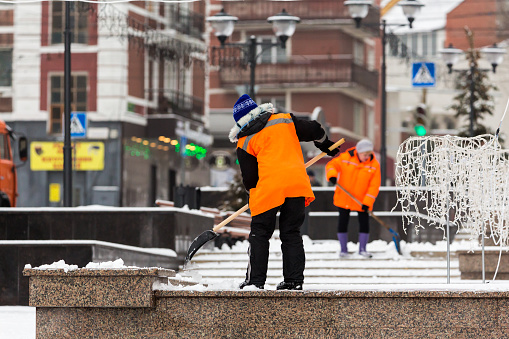 People-janitors in orange jackets cleaned the city from snow with shovels. Winter city after a snowfall.