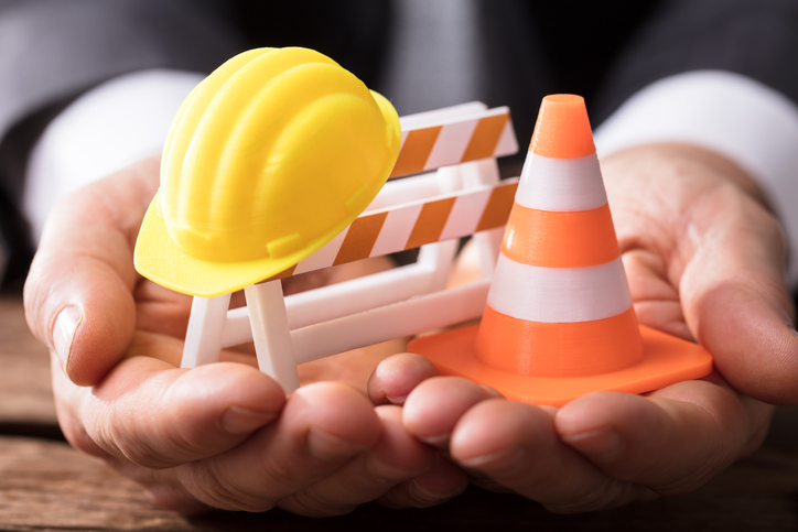 Close-up Of Human Hand Holding Barricade With Traffic Cone And Hard Hat