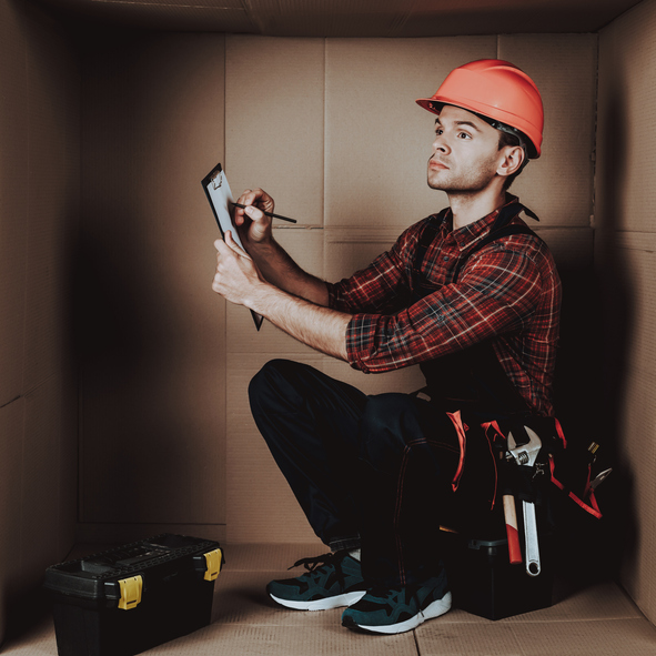 Worker in Orange Helmet Sitting in Cardboard Box. Young Man in Uniform. Uncomfortable Life. Personal Spase Concept. Uncomfortable House Concept. Young Introvert. Worker with Tools.